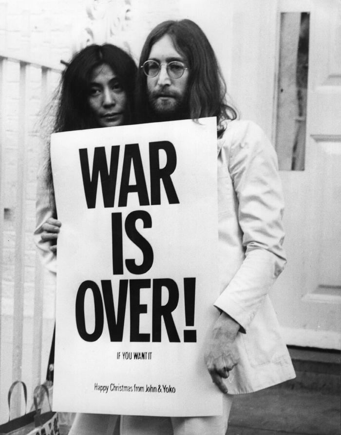Yoko Ono & John Lennon holding an original WAR IS OVER! poster.