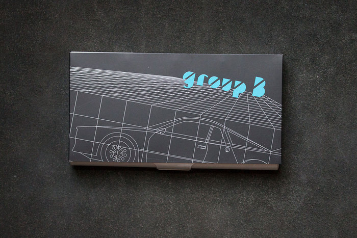 Box with a 1980s-style grid illustration and the logo shwon on an angle.