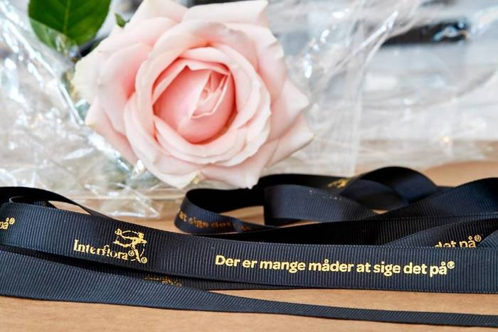 """Ribbon with the Interflora logo and the slogan (""""There are many ways to say it"""") set in Omnes Bold."""