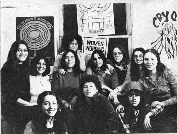 "The Chicago Women's Graphics Collective in 1972, with a ""Sisterhood is Blooming"" poster in the background."