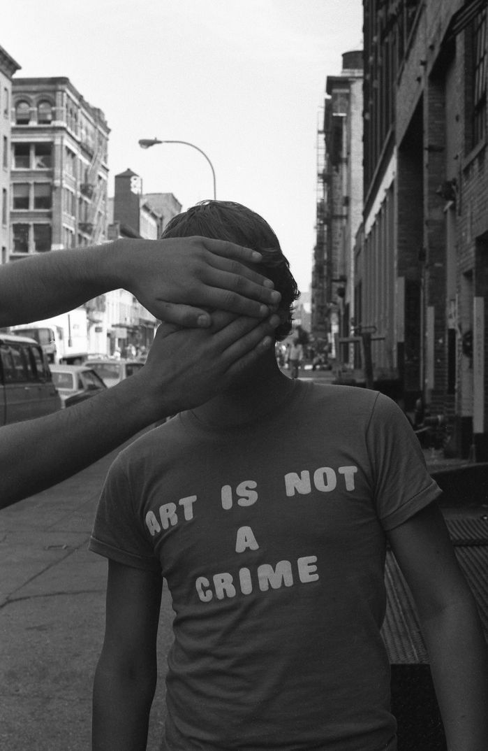 A photo outtake still from Style Wars. Hands are up concealing a grafitti artist's identity.