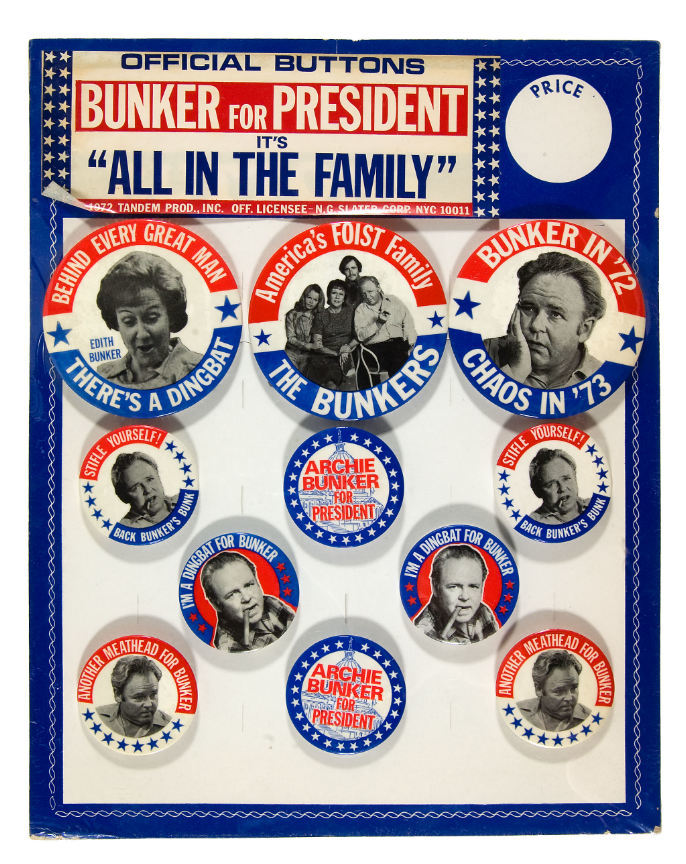 """11×14″ stiff cardboard card with fold out easel reverse. """"Official Buttons / Bunker for President / It's 'All In The Family' / © 1972 Tandem Prod., Inc Off. Licensee – N.G. Slater Corp NYC 10011."""" The card holds three 3.5″ buttons and eight 2⅛″ buttons. Most type is in all-caps . """"Official Buttons"""" uses  Bold Extended. """"Archie Bunker"""" is in ."""