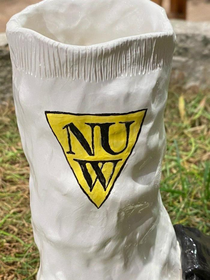 Detail of the ceramic shoe by Lota Lota showing the NUW Store branding.