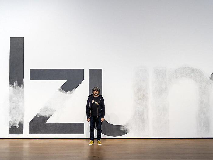 Taro Izumi posing in front of the mural that he and his team worked on in the Museum Tinguely in Basel.