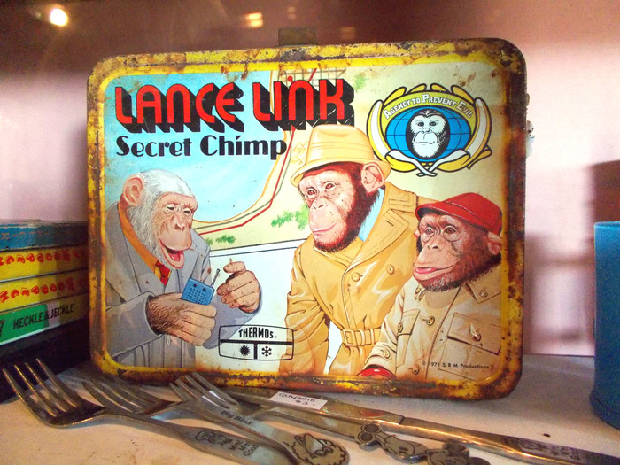 "Among the accompanying merchandise was a metal lunch box produced by Thermos (1971). Here, the ""Lance Link"" wordmark uses  Shaded (Photo-Lettering, 1970). This precursor to  (1975) was drawn by Ed Benguiat, who also helped to develop the title graphic for Planet of the Apes in 1968. [House Industries] ""Secret Chimp"" is set in . Link is shown together with Mata Hairi and his boss, Commander Darwin."