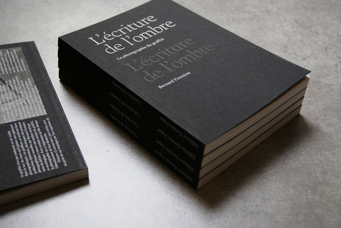 The title on the screen-printed cover features the lightest weight of the Spectral family. In a self-referential graphic allusion, it's repeated a second time, black on black.
