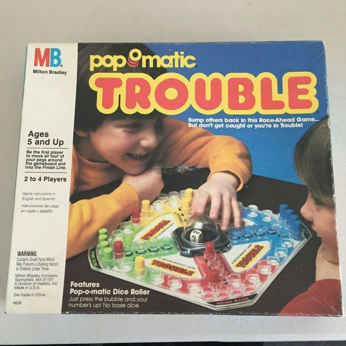 Trouble by Milton Bradley, a division of Hasbro, Inc., 1986, with game instructions in English and Spanish. Smaller texts additionally feature  and .