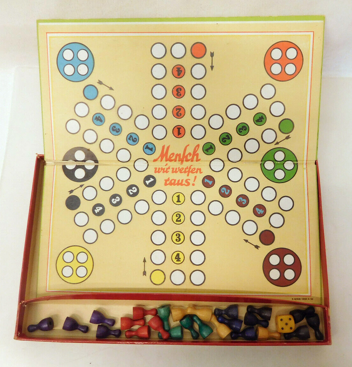 "Flipside with the layout for six players. The title at the center of the board is shown in a different lettering style, here with a long s (ſ) in ""Mensch""."