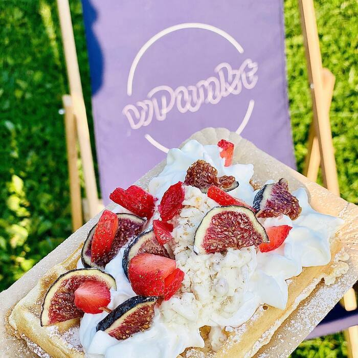 Fresh waffles with strawberries and figs, and the wPunkt logo in Saison on a deck chair.