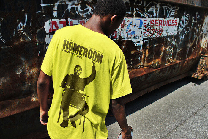 Yellow t-shirt for Homeroom, designed by Mucho, featuring Dwayne Davis with a raised fist.