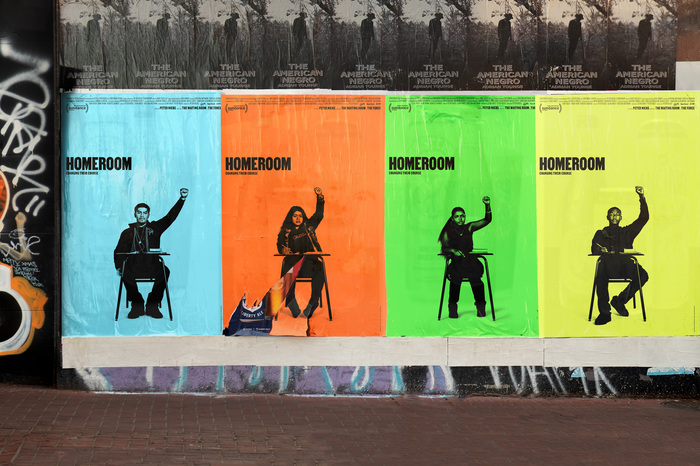 Wild postings of movie posters for Homeroom, designed by Mucho, with yellow, orange, blue, and green backgrounds, featuring multiple students with raised fists.
