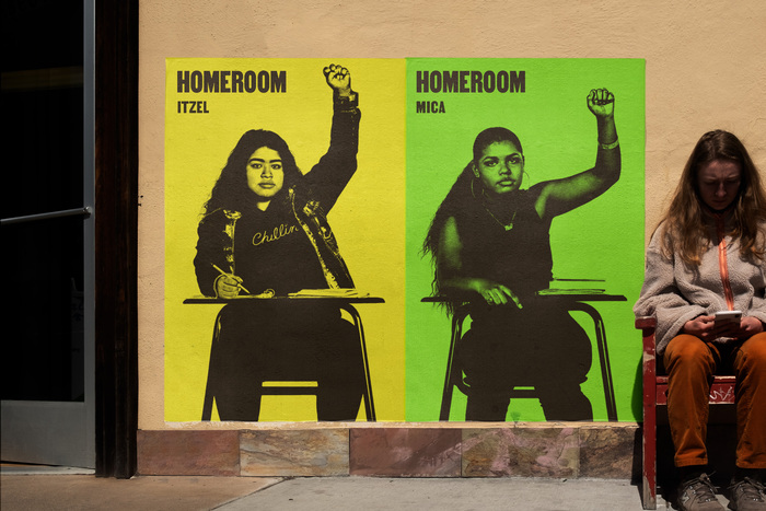 Wild posting of movie posters for Homeroom, designed by Mucho, with yellow and green backgrounds, featuring Mica Smith-Dahl and Itzel Mercado with raised fists.