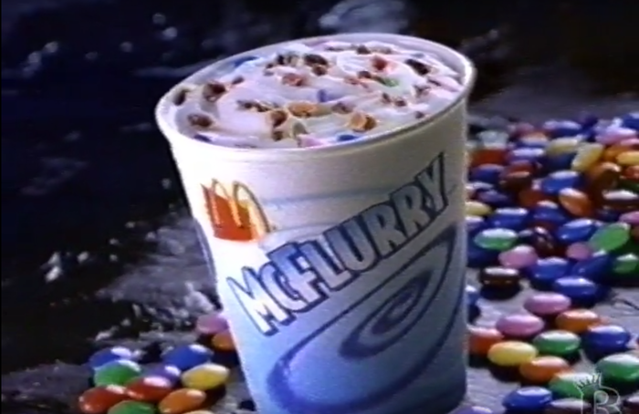 Packaging for McDonald's McFlurry ice cream, as seen in a 1998 commercial. Type is set in Bodega Sans Black, with a gradient and shadow applied by the designer.