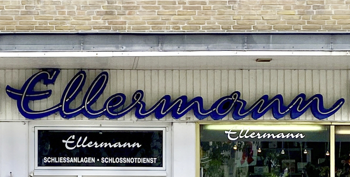Detail. The neon tube adds an inline – or heartline – to the bold brush script. It closely follows all details of the design, including Slogan's peculiar letter a which uses the Kurrent construction. The terminal swash falls under artistic license.