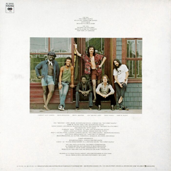 Back cover of a Canadian pressing from 1975. From Wikipedia:   The back photo for the album featured six members of Springsteen's backing E Street Band standing in a doorway of an antique store on Sairs Ave in the West End section of Long Branch, New Jersey.