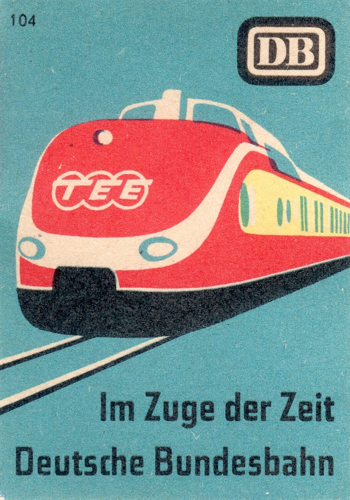 """""""Im Zuge der Zeit"""" means both """"in the course of time"""", but also """"in the train of today"""". The depicted trainset was manufactured in 1957. The Trans Europ Expressnetwork was set up in the same year."""