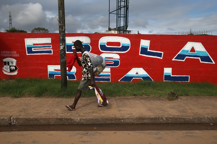 A man passes an Ebola awareness mural on October 2, 2014 in Monrovia, Liberia. More than 3,200 people have died in West Africa due to the epidemic.