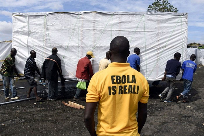 A man looks on as workers set up a new treatment centre as part of the fight against the deadly ebola virus in Monrovia, Liberia.