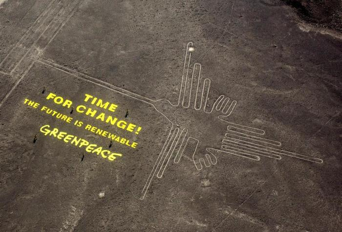 Greenpeace activists stand next to massive letters delivering their message next to the hummingbird geoglyph in Nazca, Peru.