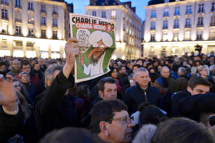 "A man holds up an edition of Charlie Hebdo magazine as people gather on the Place Royale in Nantes, western France, on January 7, 2015, to show their solidarity with the victims of the attack on the offices of the satirical weekly in Paris. Muhammad's speech bubble in the cartoon reads, in French, ""A hundred lashes if you don't die laughing."""