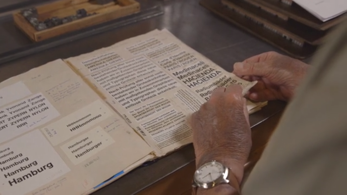 """Alfred Hoffmann going through his father's""""Helveticajournal"""".Still from the promotional film."""