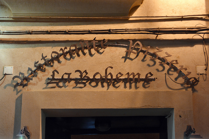 The sign above the entrance uses yet another broken script. Lucida Blackletter (1992) doesn't belong to the same group as the others, though. With its more cursive forms, it can be described as a contemporary Bastarda. It is less hard to decipher than a Textura. However, this advantage is ruined by the unfortunate mounting/lighting which renders the letters almost illegible.