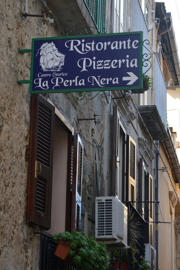 "The descending 'P' has been clipped in ""Pizzeria"". The last line appears to be stretched."