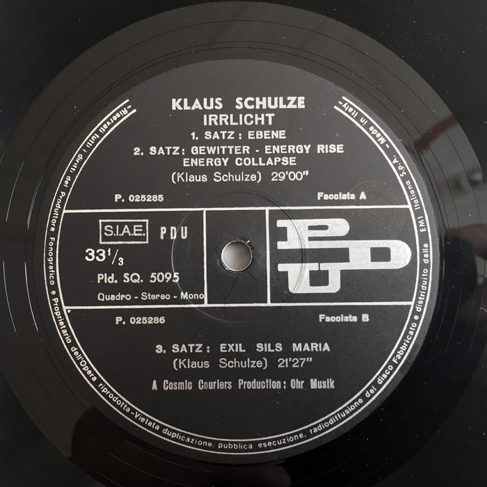 "The record label on the A side uses a mix of different sans serif typefaces for information in a more classic look than the rest of the album, including Semplicità Nera (for ""Klaus Schulze"" — the asymmetrical 'U' is the giveaway) and Cairoli, Nebiolo's version of the German grotesque series best known as Aurora-Grotesk. As the record was produced in Italy, Mr. Schulze was probably not involved in the design of this label, and the record manufacturer simply used what was common, and at hand. The labels of the original release on Ohr show a human ear — ""macht auf das [Ohr]"" (""open up the ear""), in tightly spaced Helvetica."