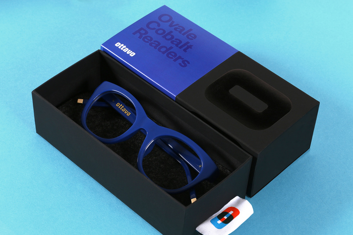 """Mucca """"designed the packaging with […] the credo that form follows function: a belly band allows a single box to be used for many combinations of lens powers, shapes, and colors; and the tag on the glasses sleeve doubles as a pull to upon the box."""""""
