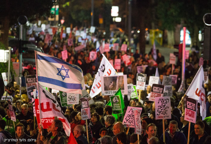Peace Now flags and signs at a rally in Tel Aviv.