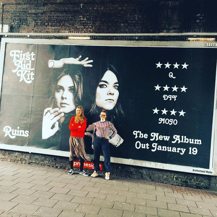Swedish duo in front of advert in Shoreditch, London