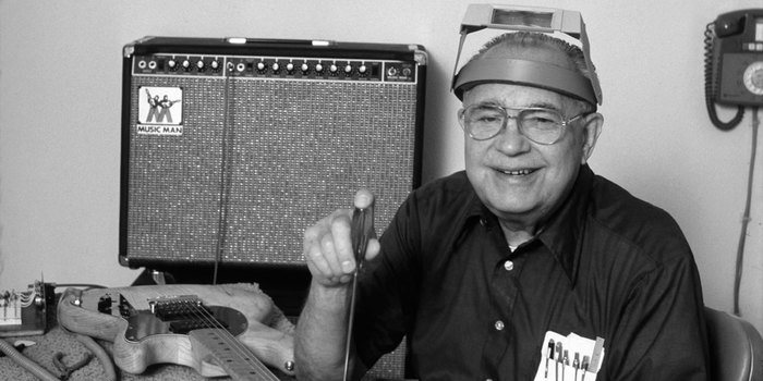 Leo Fender at his CLF Research workshop with a Music Man amp in the background and a Music Man guitar on the table.