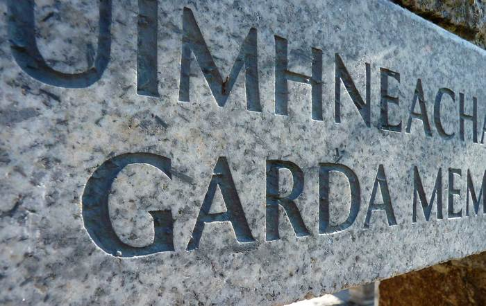 Detail showing the carved dual-language granite plinth leading into the memorial garden.