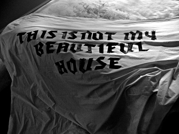 Nada Prlja — This is Not My Beautiful House. Letters pressed into the bed sheet by artist's body while sleeping. Bed sheet 2x1.6m, printmaking ink, 7 hours. The text is taken from the lyrics to the song 'Once in a lifetime' by Talking Heads, 1981. Photo the artist.