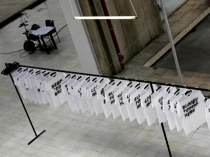 Nada Prlja — Strike. Installation, 2008. Industrial shirt railing, 10m, 100 hand painted T-shirts, 100 hangers. Image from the solo exhibition at the Museum of Contemporary Art, Skopje, Macedonia. Courtesy the artist