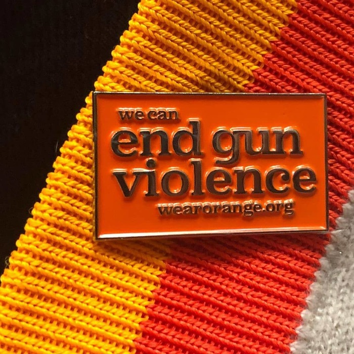 "Metal pin with raised letters. In the ""end gun violence"" slogan, Jubilat is used with its alternate single-storey g."