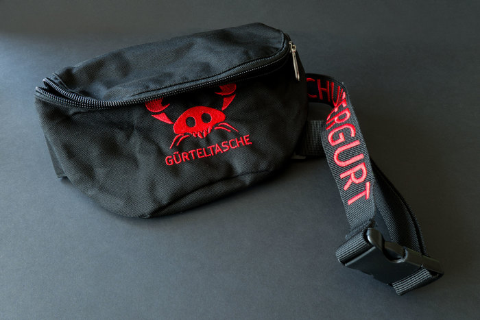 The print on the font of the fanny pack is the German translation of belt pouch – GÜRTELTASCHE. The belt itself reads SCHULTERGURT, German for shoulder-belt.
