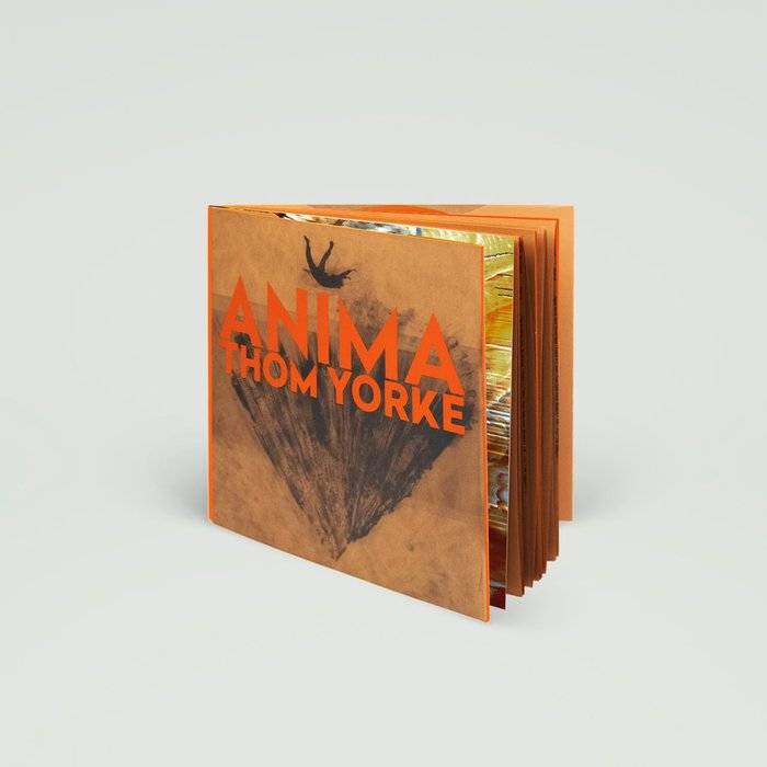 """A beautiful hardback book containing both the lyrics and many strange drawings done in pencil by Stanley Donwood & Dr Tchock. Orange 180 gram double vinyl with an additional 10th track (Ladies & Gentlemen, Thank You For Coming). […] Printed onto Italian Fedrigoni special brown material paper and section sewn, the book is made up with an exposed orange cloth spine and orange gilt edging and finished with bodonian binding."""