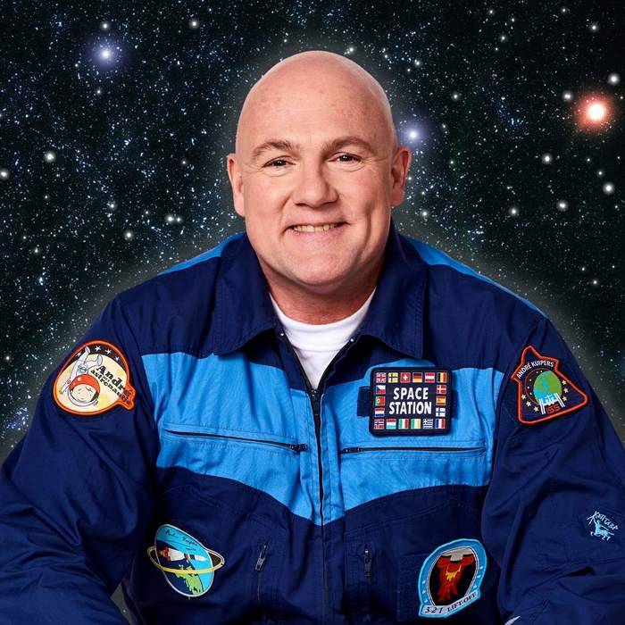 "André Kuipers with a ""little astronaut"" patch on his right arm."