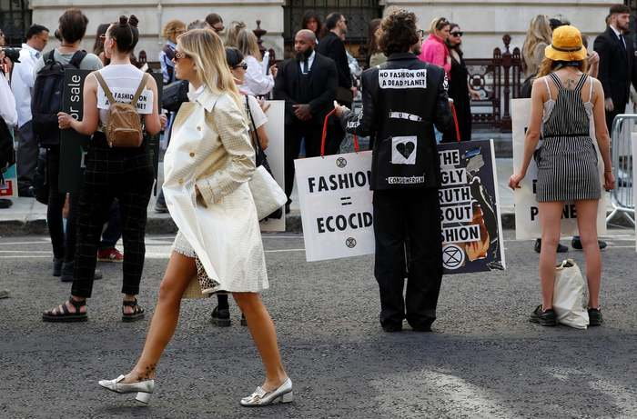 September 2019. A show-goer walks past Extinction Rebellion protesters as they demonstrate against London Fashion Week.